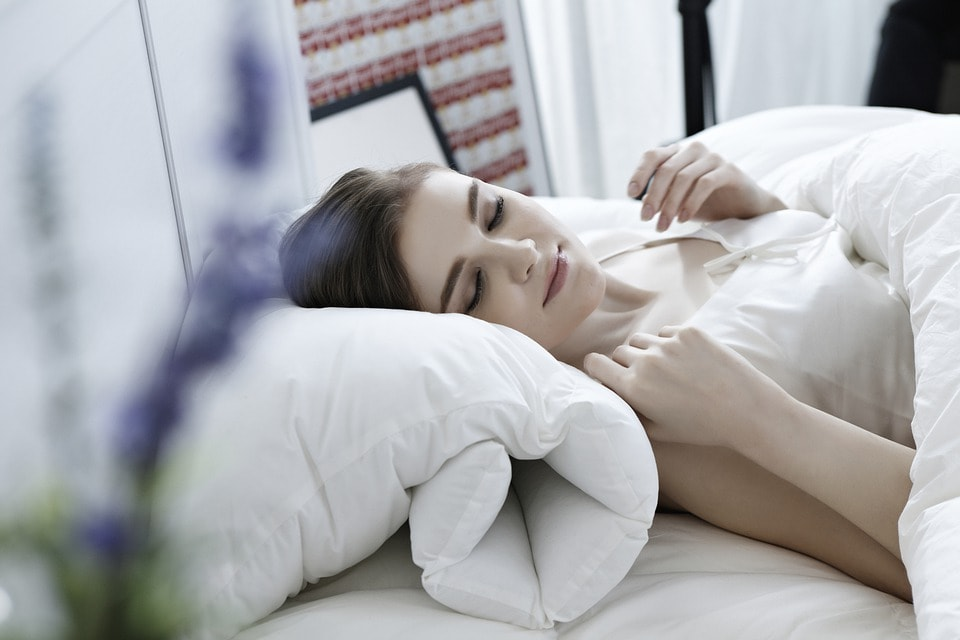 A woman sleeping on back at her bed